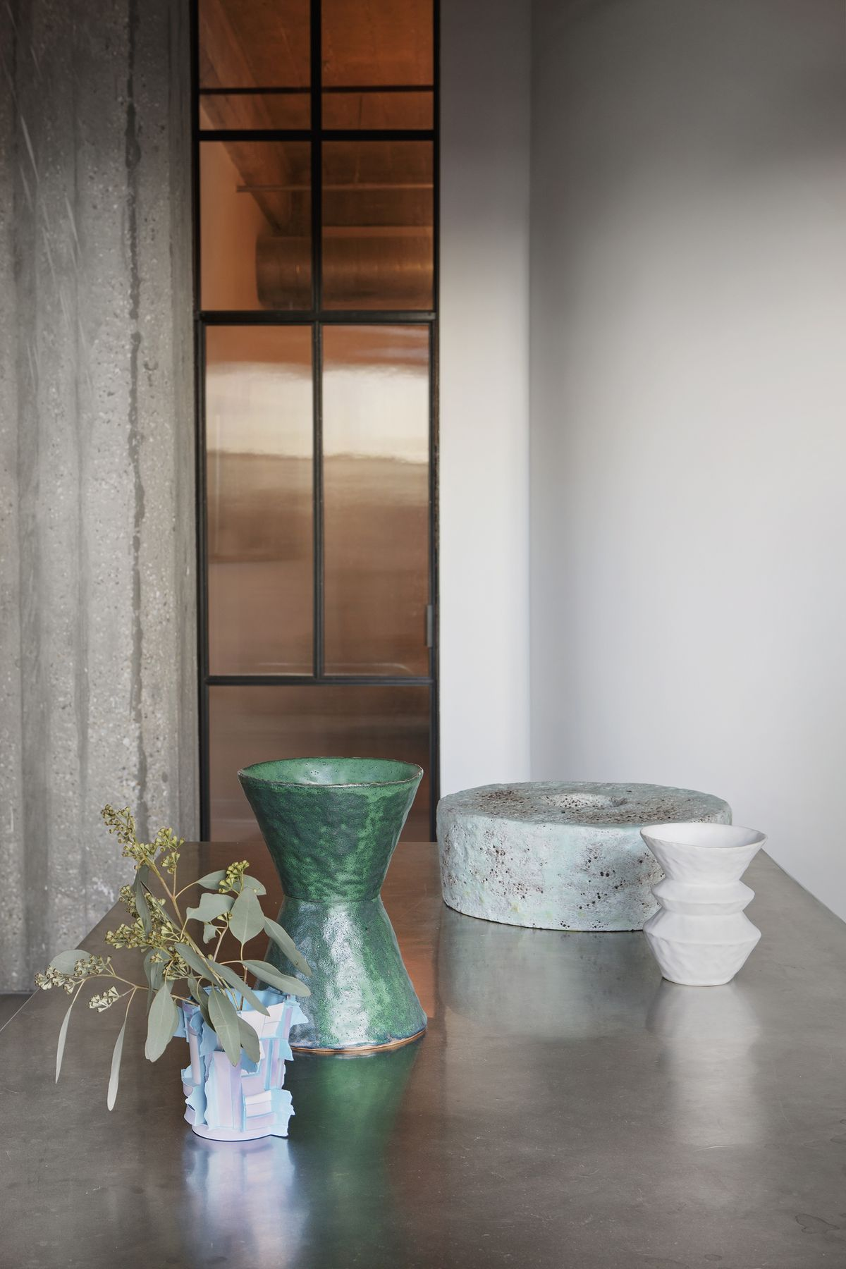Vases and other assorted objects sit on a metallic surface. in the distance is a window and a grey concrete wall.