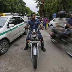 In this Tuesday, Aug. 21, 2012 photo, Pradeep Kumar rides his motorbike as he heads to work at the Deen Dayal Upadhyay Hospital in New Delhi, India.  Kumar and 20 other bouncers have been hired to protect doctors as well as keep the emergency and labor rooms from filling up with patients' often agitated relatives and friends.