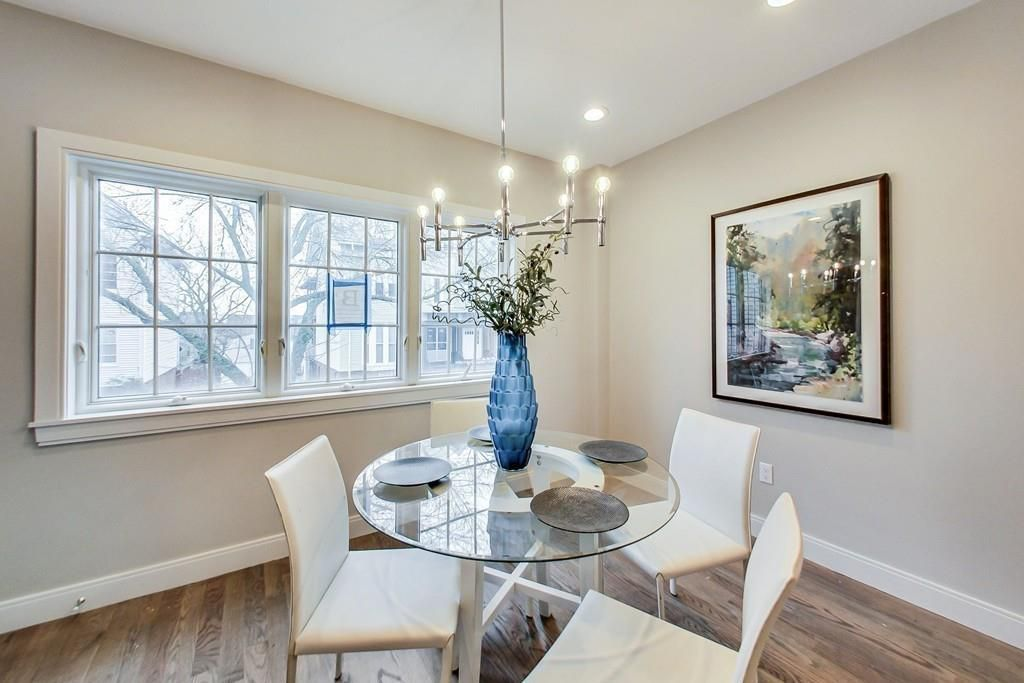 An open dining room area in a corner with a table and chairs.