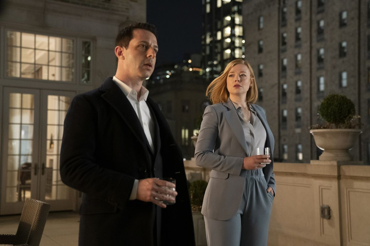 Kendall and Shiv, both holding drinks, speak on a balcony at night in Succession