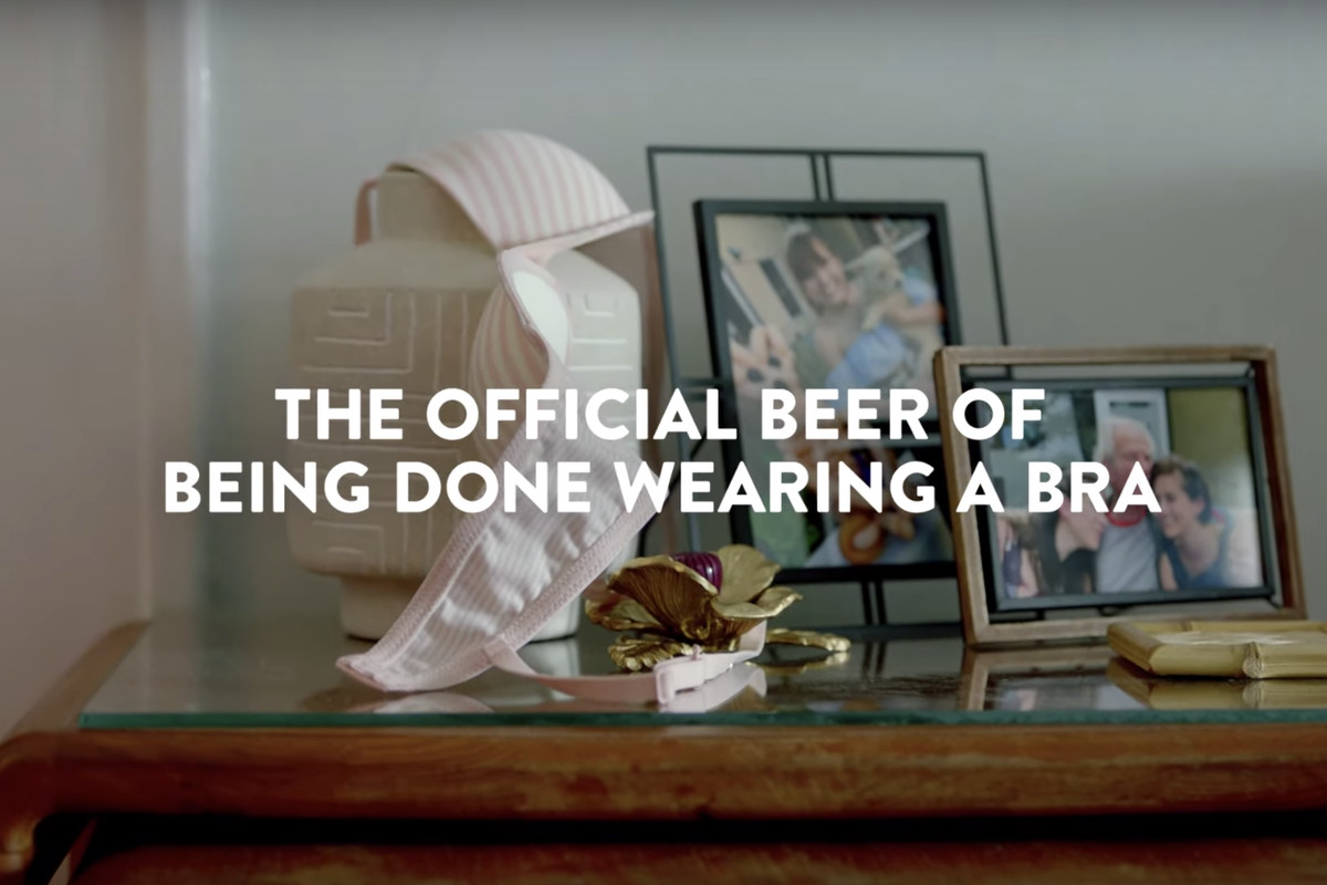 """A woman's discarded bra lays slung over framed photos on a glass side table with the words """"The official beer of being done wearing a bra."""""""