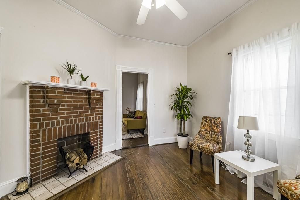 Small den with brick fireplace, chairs, table and lamp.