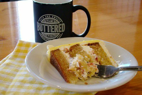A slice of lemon and strawberry cake with thick layers of fruit-studded butter cream sits on a small white plate with a fork ready to cut into it. A black cup with The Buttered tin logo sits beside it on a small table.
