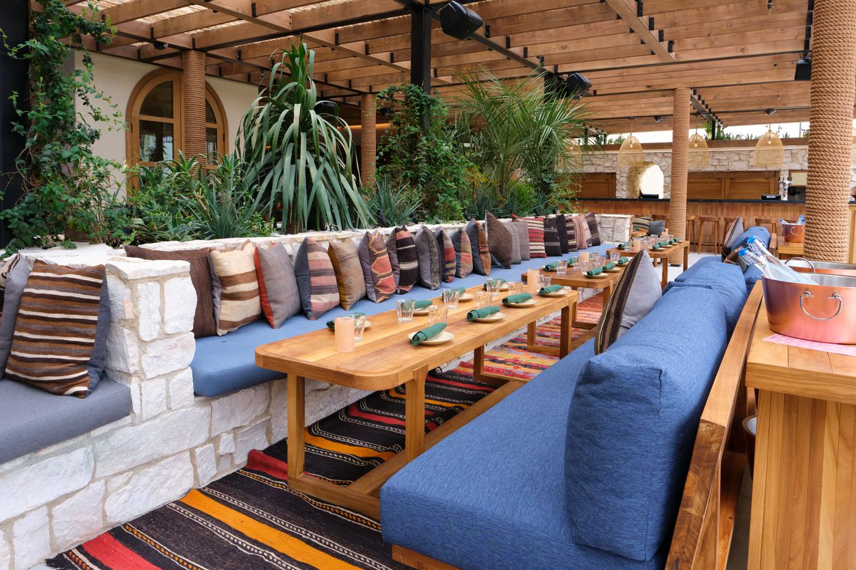 A patio with blue benches filled with colorful pillows