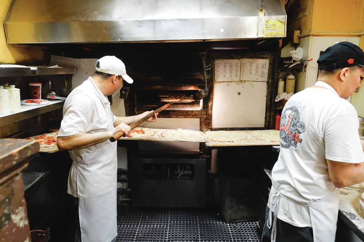 Two employees stand in the kitchen at Regina, with one checking on a pizza in the oven and other prepped pizzas lined up and ready to cook