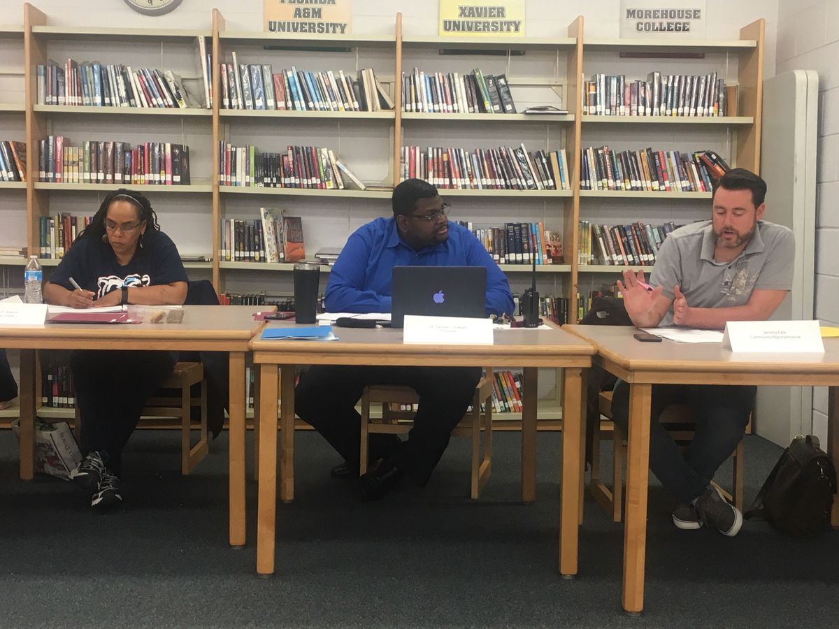 Uplift Principal Tyrese Graham, center, listens to Local School Council member Jeremy Falk at a March council meeting in the school's library. Council Chair Sharon Adams sits to Graham's left.