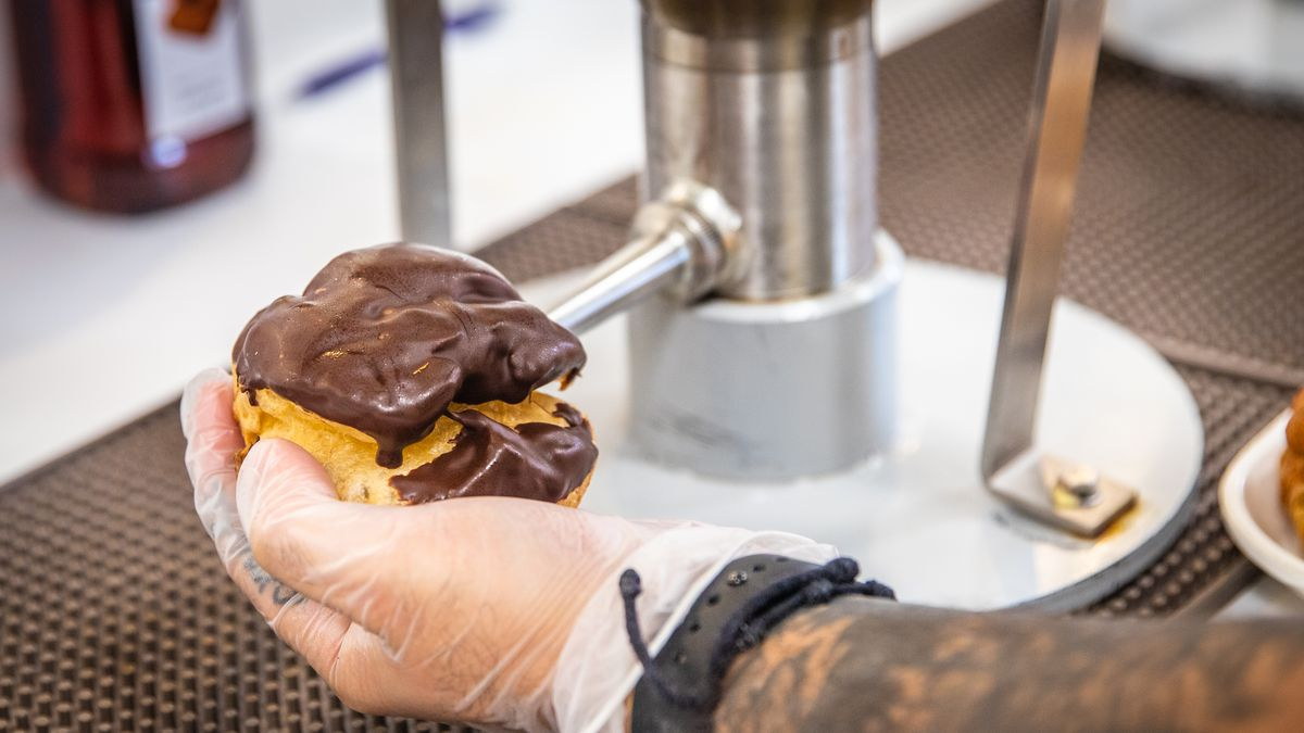 A person wearing black gloves fills a pastry shell with cream through a metal spigot.