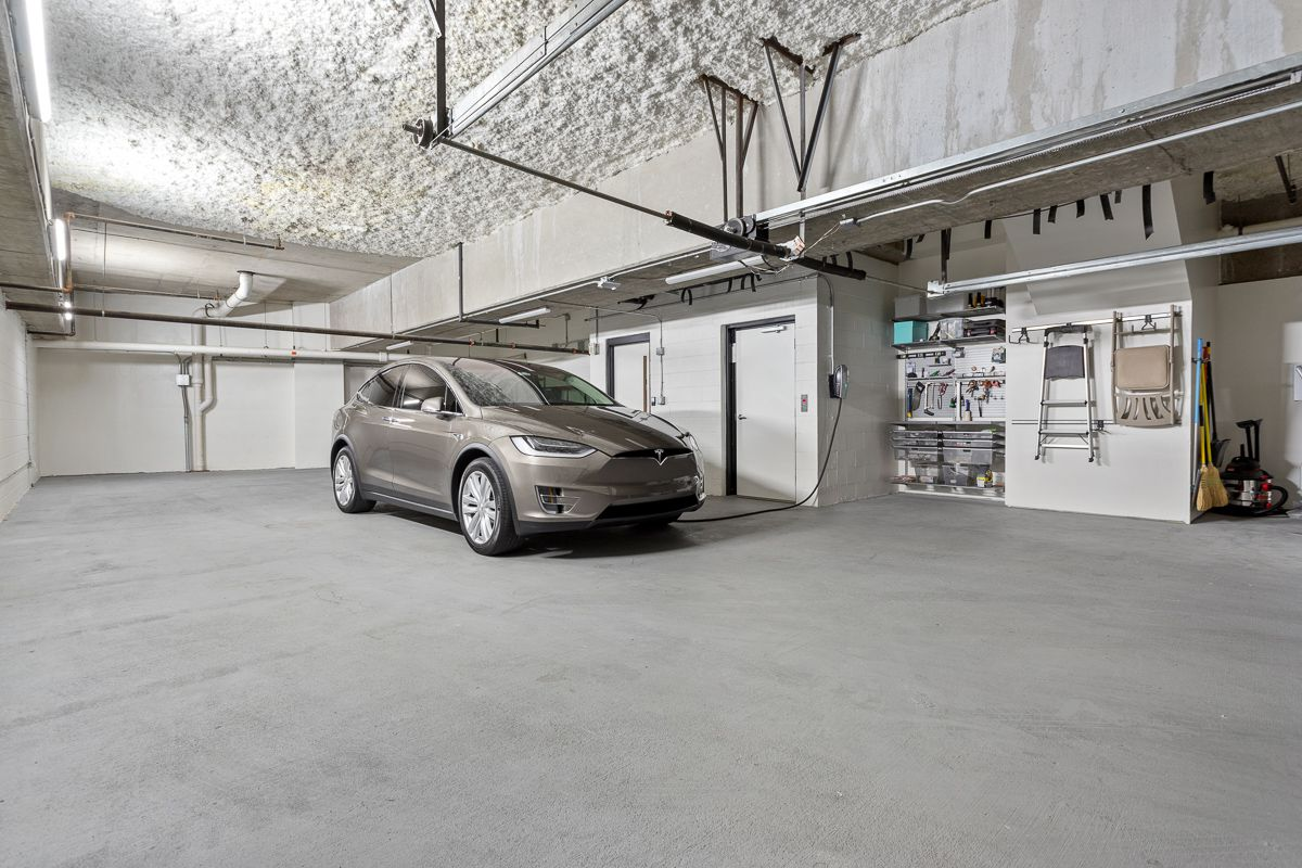 A six-car garage with white walls that includes a workshop space and Tesla charger.