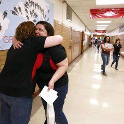 Keri Graybill, the Granite School District Teacher of the Year, hugs Melinia Pugsley at Granite Park Junior High School Friday, May 23, 2014, in Salt Lake City.