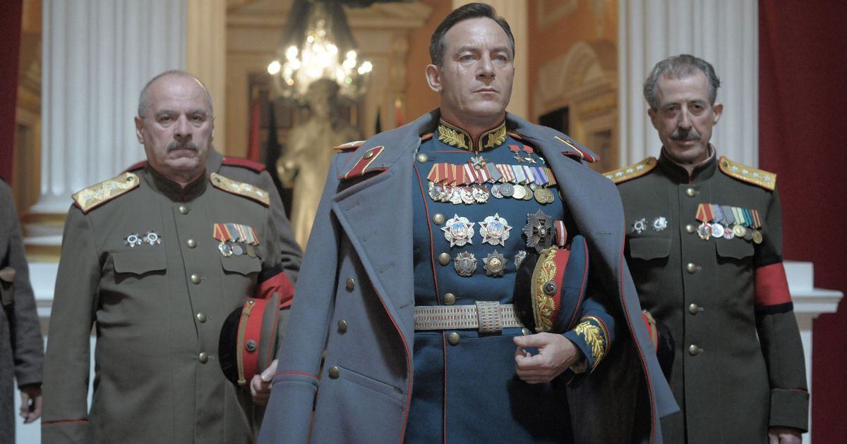 three Russian soldiers wearing uniforms and medals pass through the Ballroom