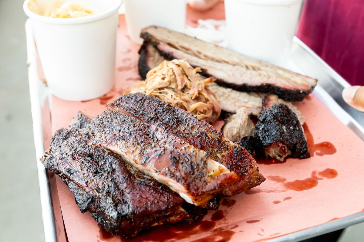 A spread of ribs, brisket, and pulled pork served on a paper-lined sheet tray