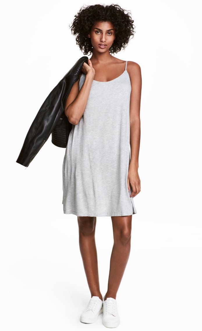 A model wearing a gray slip dress and jacket