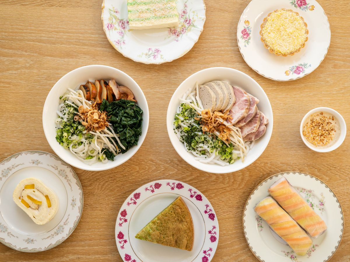 A table at Berlu is covered in bowls of noodle soup, slices of cake, and other pastries