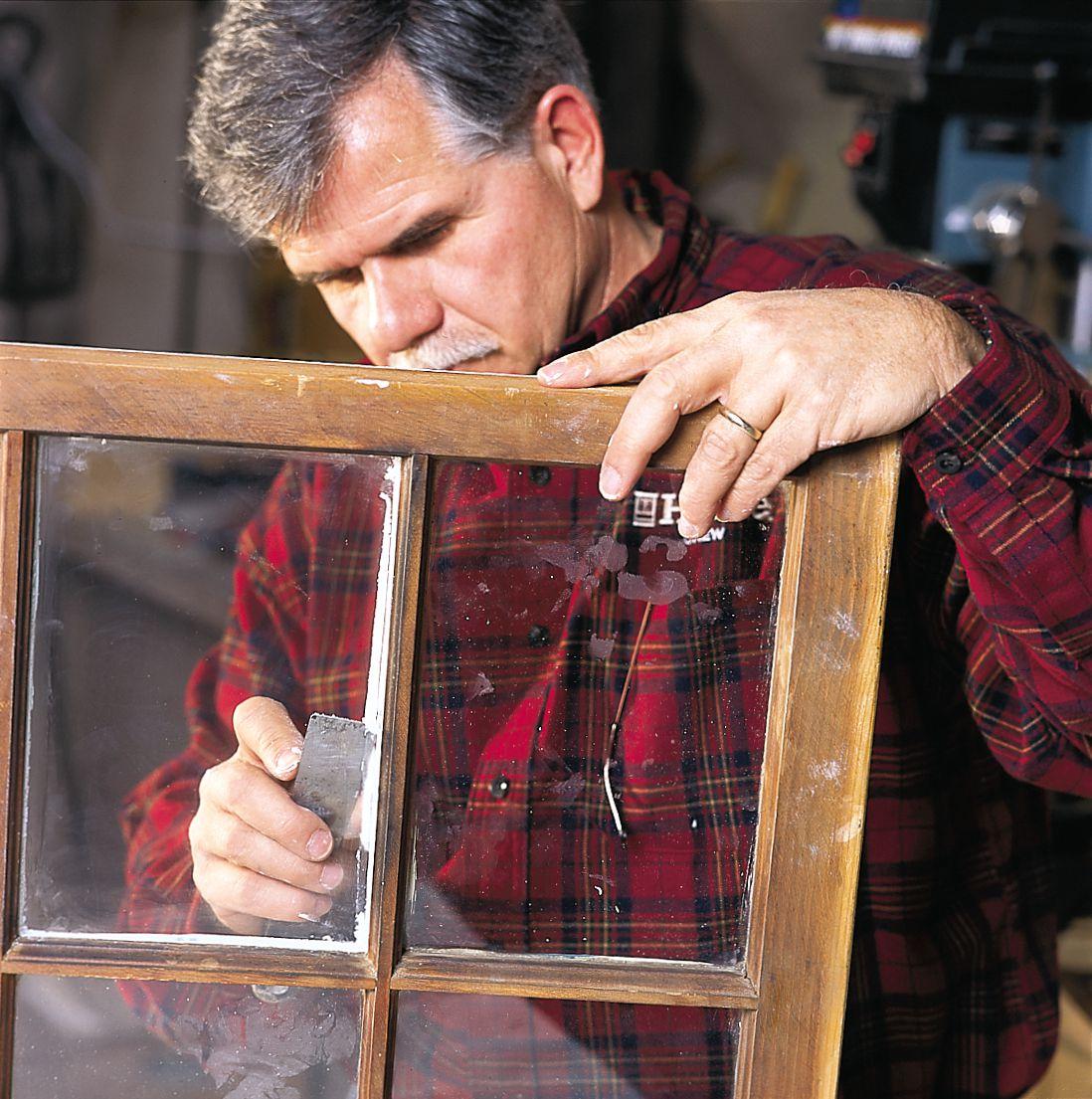 Person reglazing drafty window.
