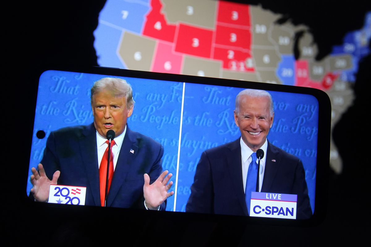 A photo illustration of President Donald Trump and Democratic presidential candidate Joe Biden on a smartphone screen, in front of an electoral map.