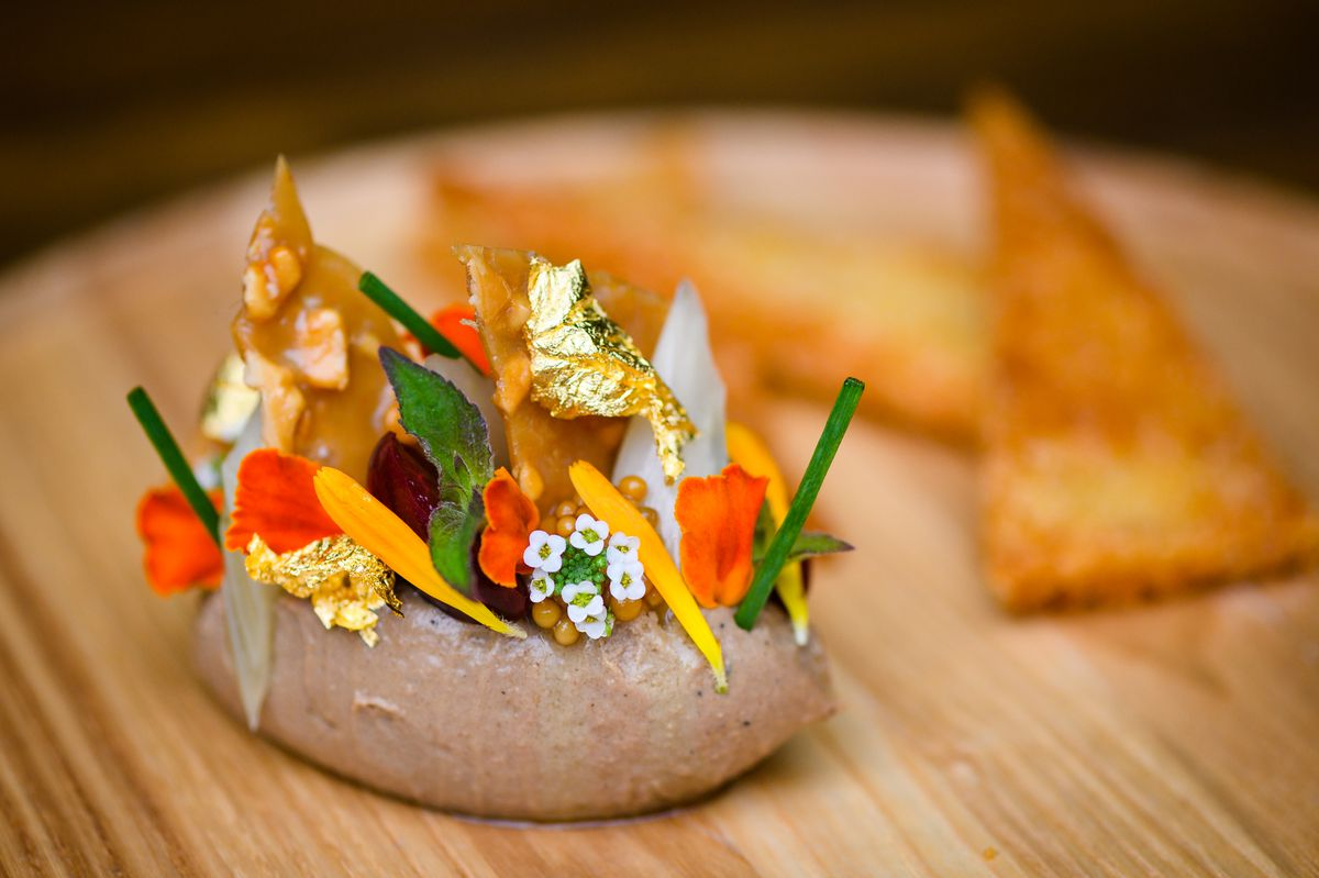 Chicken liver mousse with peanut brittle, peach and celery, and a side of focaccia crostini on a wooden plate
