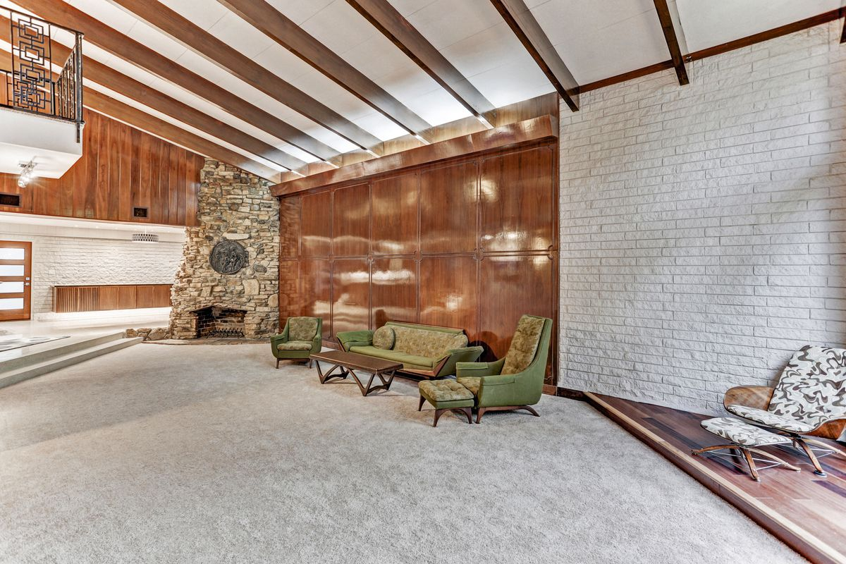 A living room has carpet, a stone fireplace on one end, and a green living room couch set.