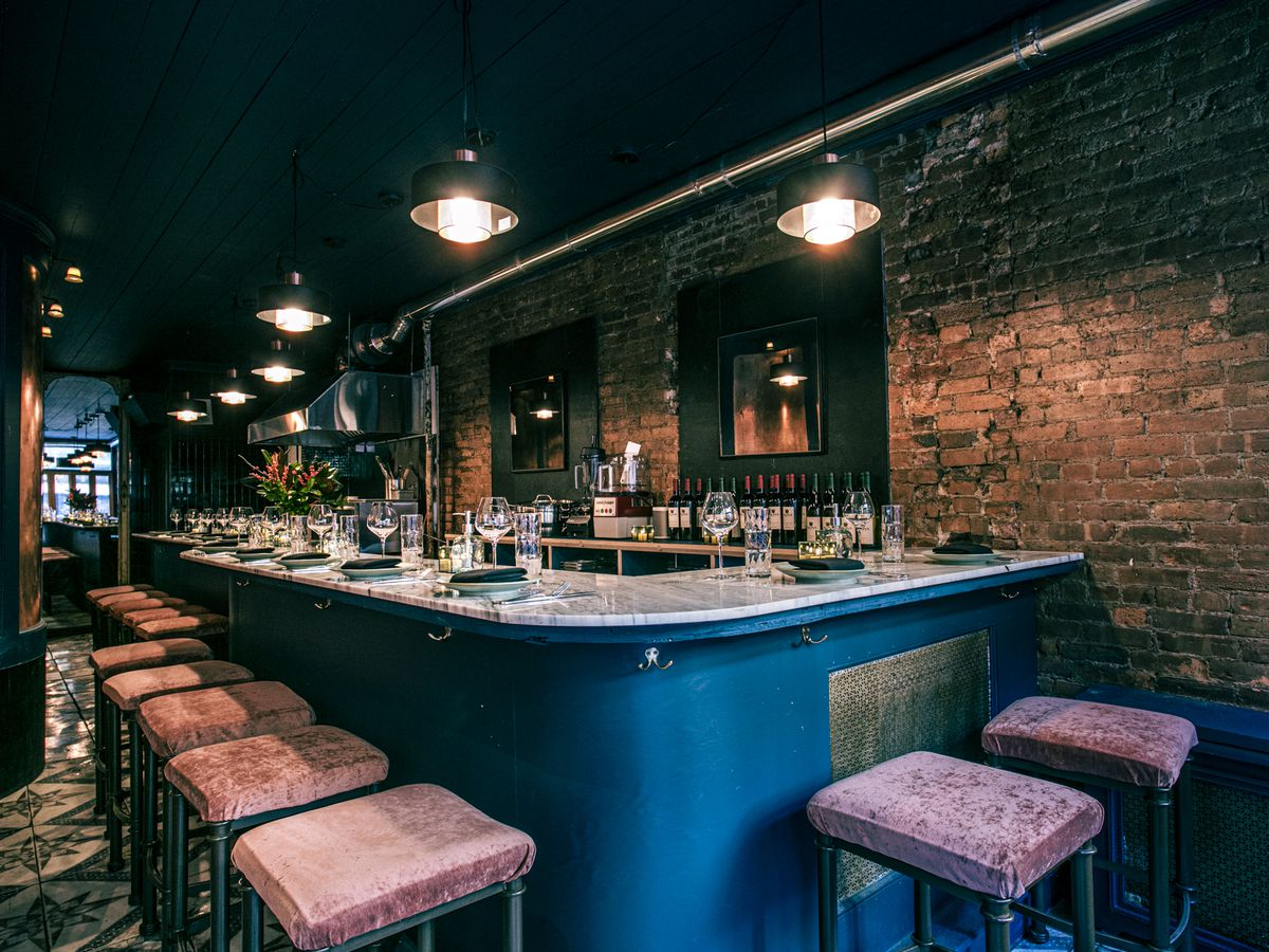 A grey marble-top restaurant bar against a brick wall, with plush pink velvet backless bar stools set against the bar
