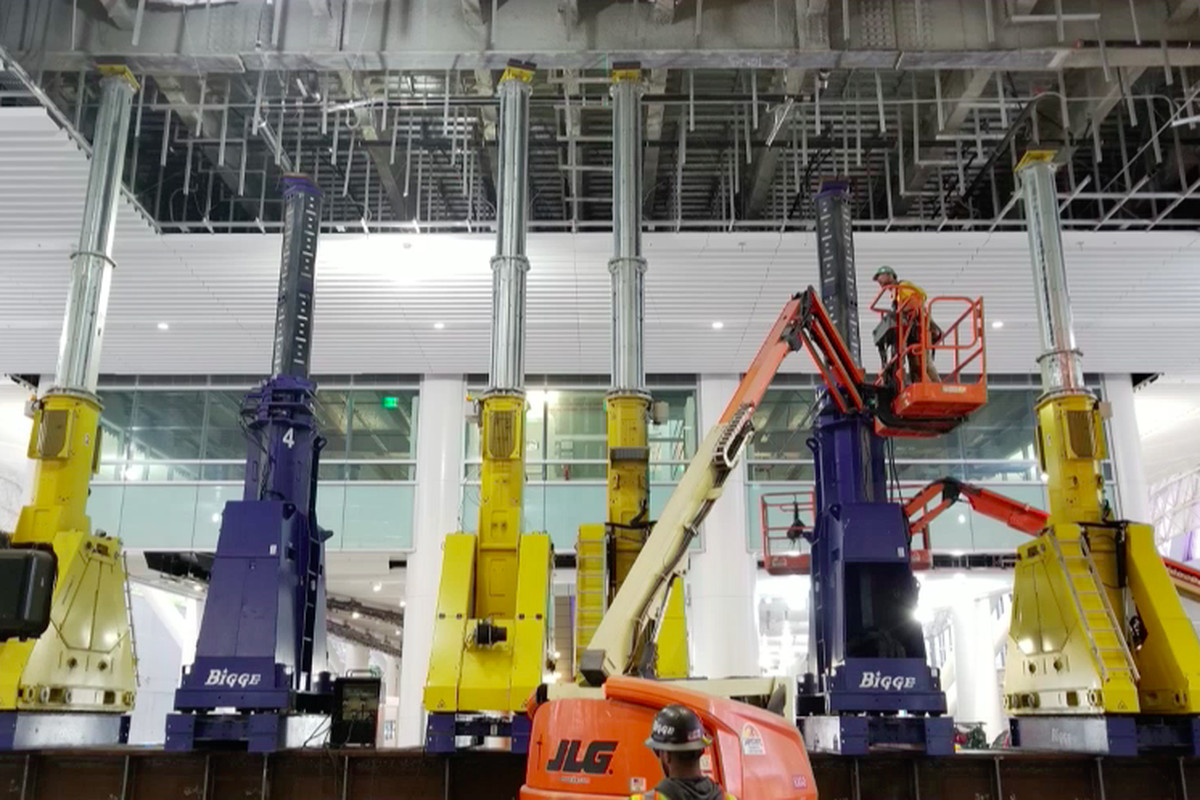 Heavy machinery and extendable jacks holding up the ceiling of part of the Transbay Transit Terminal, with a worker in a scissor lift inspecting them.