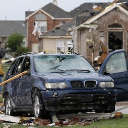 A damaged vehicle is seen as area residents survey the tornado damage to their neighborhood Tuesday, April 3, 2012, in Forney, Texas. Tornadoes tore through the Dallas area Tuesday, peeling roofs off homes, tossing big-rig trucks into the air and leaving flattened tractor trailers strewn along highways and parking lots.