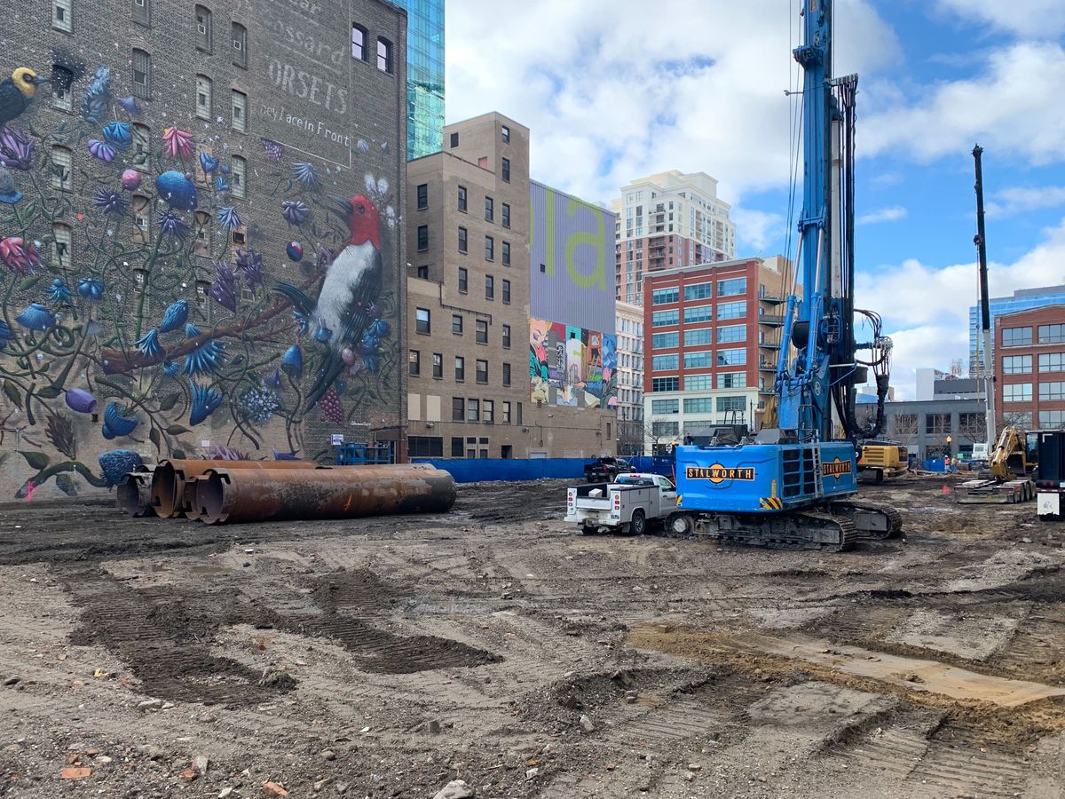 A dirt lot between two building with heavy machinery drilling down into the earth.
