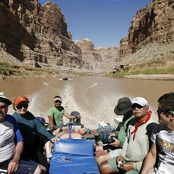 Ray Grass, left, Mary Hughes, Brian Martinez, Mike Hughes, Chowgule and Alex Rogers motor out of the canyon on a modified Zodiac boat. The Hughes family said the river trip was everything they expected and more.