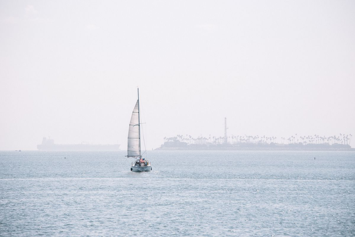 A sailboat on the water, with an island faintly visible in the distance through haze