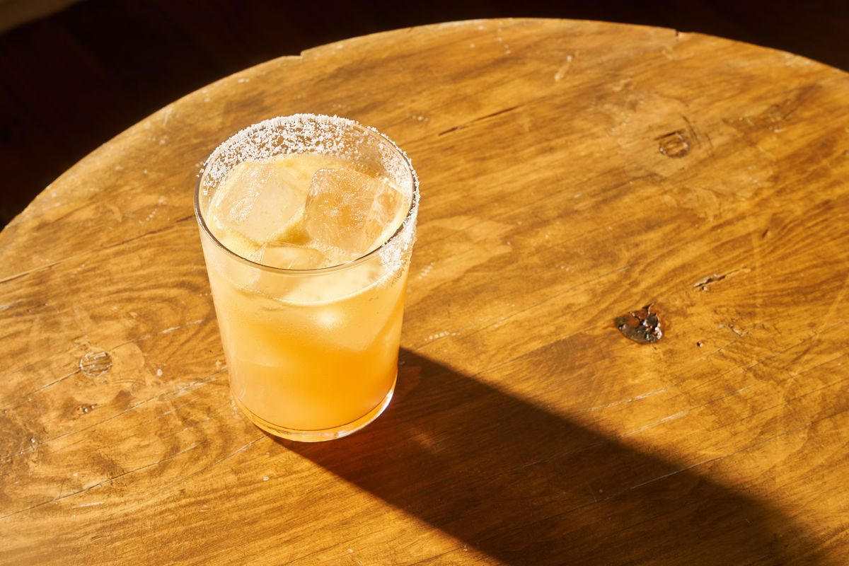 A yellow-orange cocktail with a salted rim and large ice cubes rests on a wooden table with a long shadow