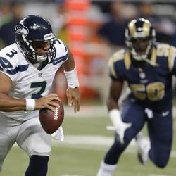 Seattle Seahawks quarterback Russell Wilson runs from St. Louis Rams outside linebacker Jo-Lonn Dunbar during the first half of an NFL football game Sunday, Sept. 30, 2012, in St. Louis.