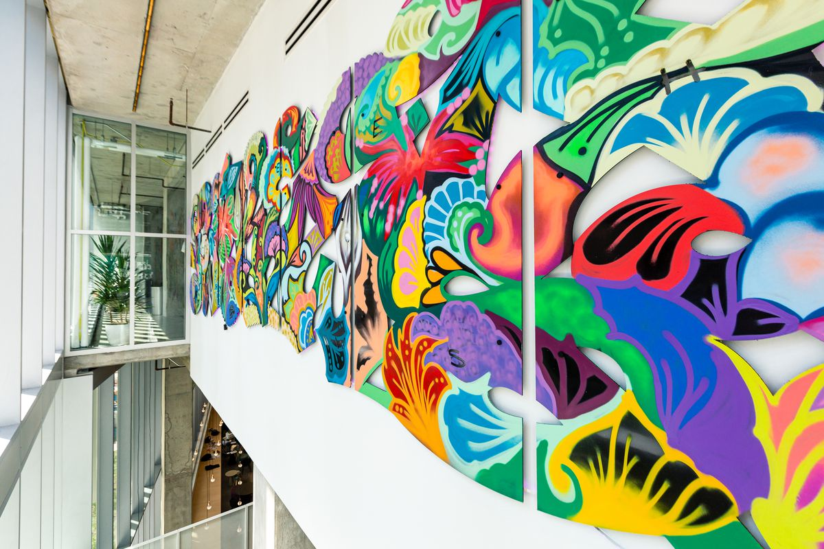 A long white wall above a lobby space with spray painted flowers arranged in a artful pattern. It is opposite a glass wall facing the outdoors.