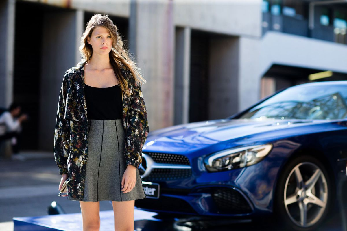 A woman in a black top, gray skirt, and jacket standing in front of a blue car.