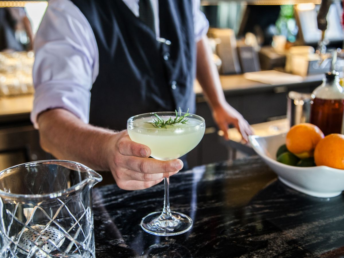 A bartender holding up a cocktail in a coupe glass over the bar