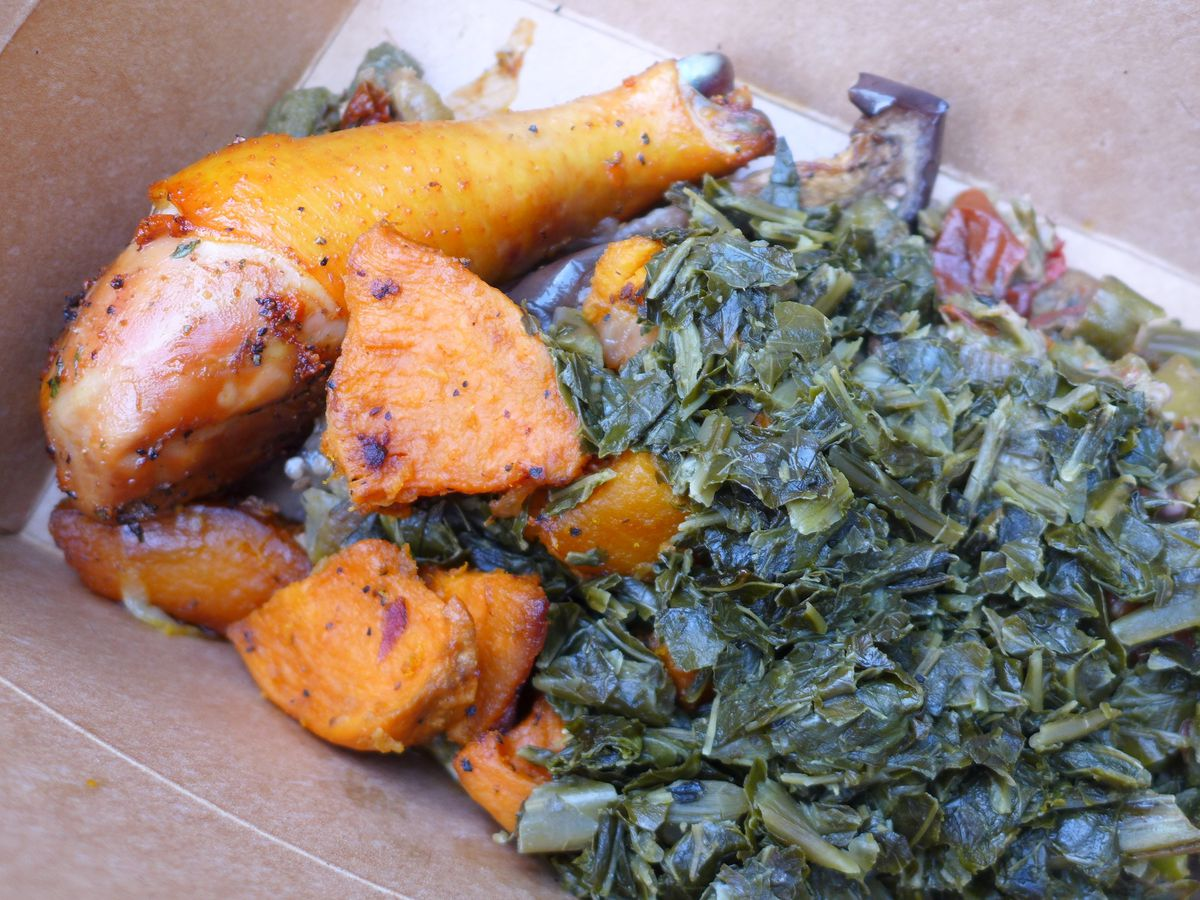 Orangeish roast chicken, sweet potatoes, and chopped greens in a square cardboard box.