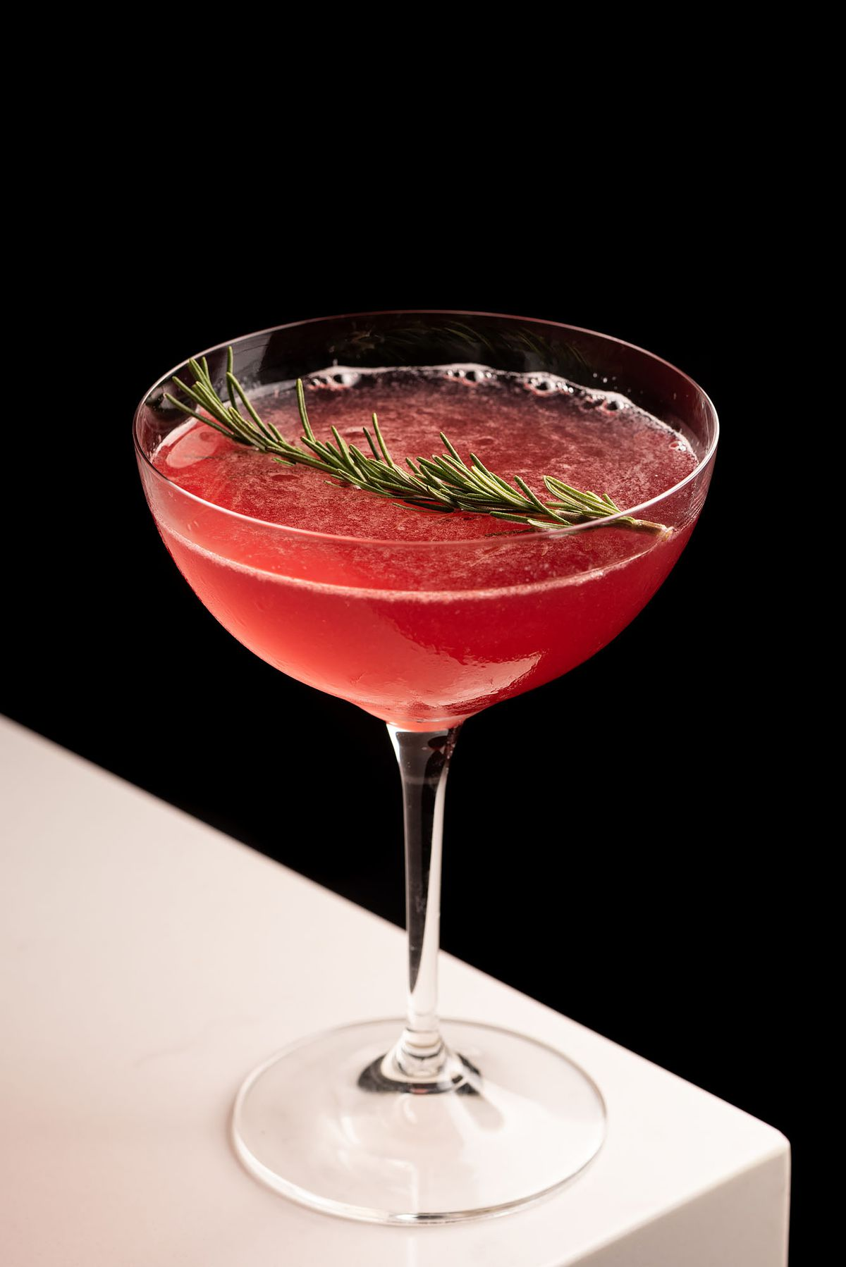 A red hued cocktail with a sprig of rosemary.