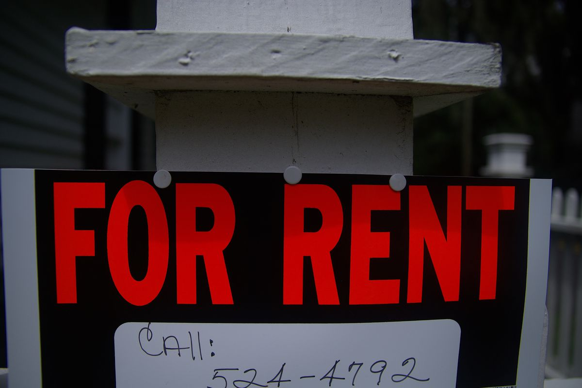 "Orange and black ""For Rent"" sign on white post"