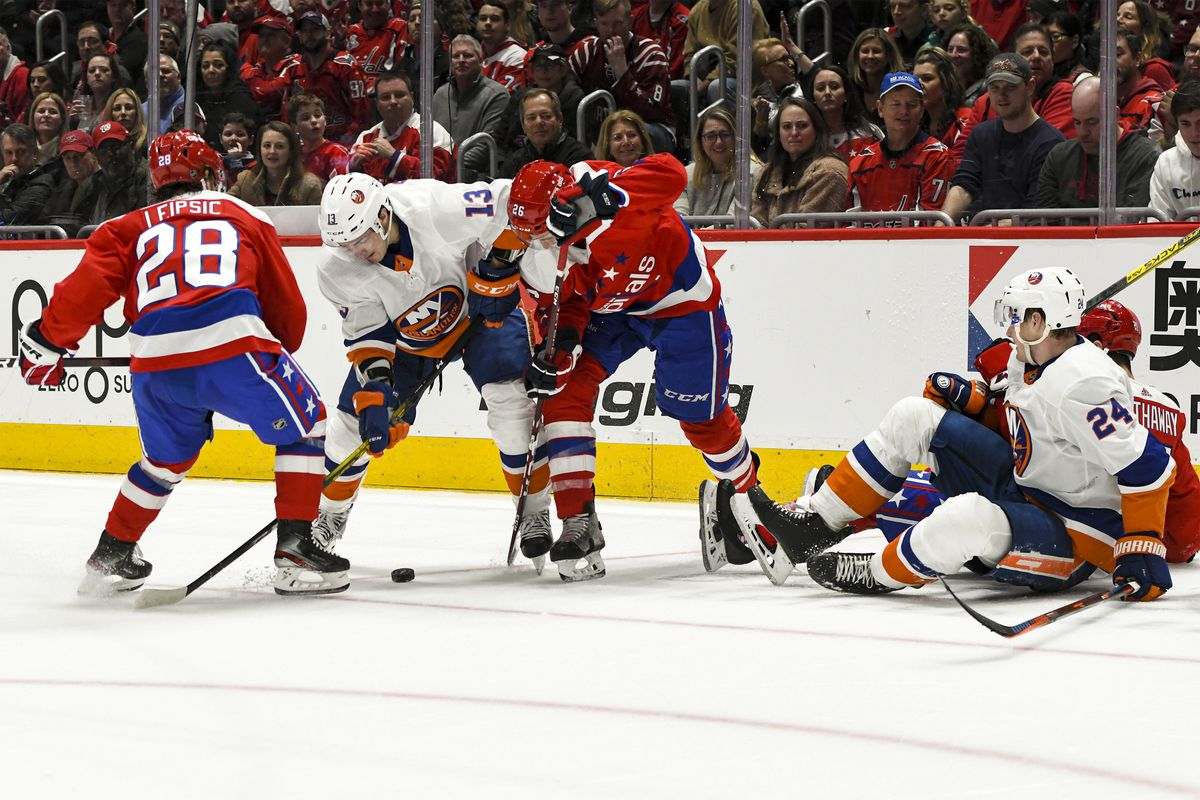 New York Islanders center Mathew Barzal moves the puck against Washington Capitals left wing Brendan Leipsic and center Nic Dowd in the second period on February 10, 2020 at the Capital One Arena in Washington, D.C.