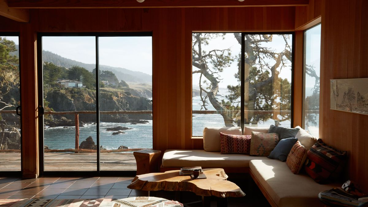 A living room overlooking the sea and some cliffs containers an L-shaped bench with 10 throw pillows. There is also a rustic, wooden coffee table and a geometric rug.