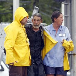 FILE - In this Thursday, Aug. 30, 2012 file photo, Larry Bailey, center, found in floodwater caused by Hurricane Isaac, is helped to safety in Slidell, La. When a Florida man saw the news photo of Bailey, who at the time was unidentified, rescued from Isaac's floodwaters, he was sure it was his brother. It wasn't — but the mistaken identity started a search that ultimately reunited Bailey, who has been homeless, with the two daughters he hadn't seen in 16 years.