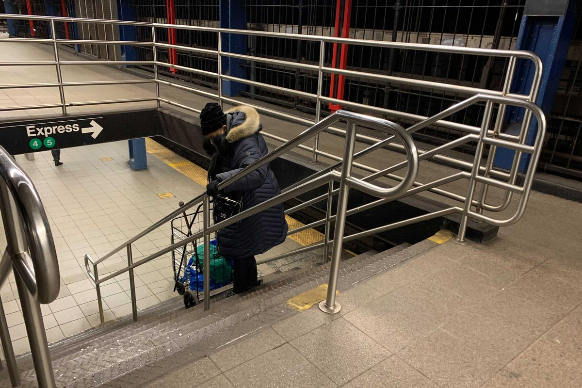 Barbara E., 63, who uses a cane to walk, carries a cart up the stairs from the southbound 4/5/6 platform at 14th Street. Jan. 25, 2021.