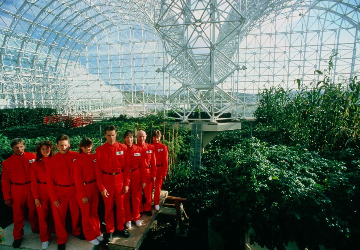 seven men and women in red suits in the Biosphere 2 in a still from the documentary Spaceship Earth