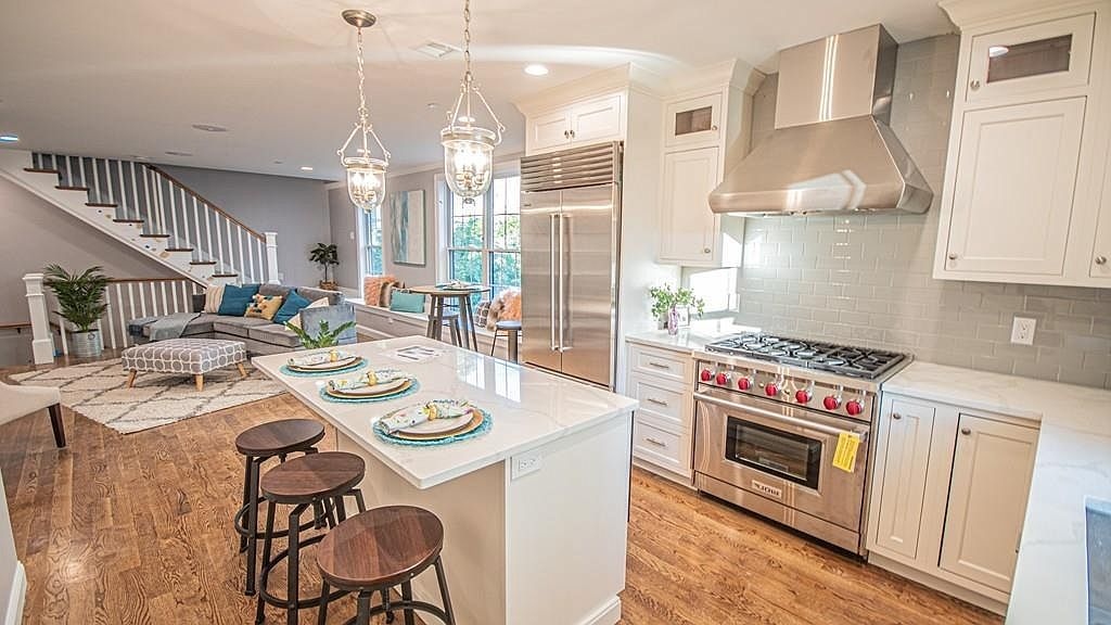 An open kitchen with an island and three stools in front of the island.