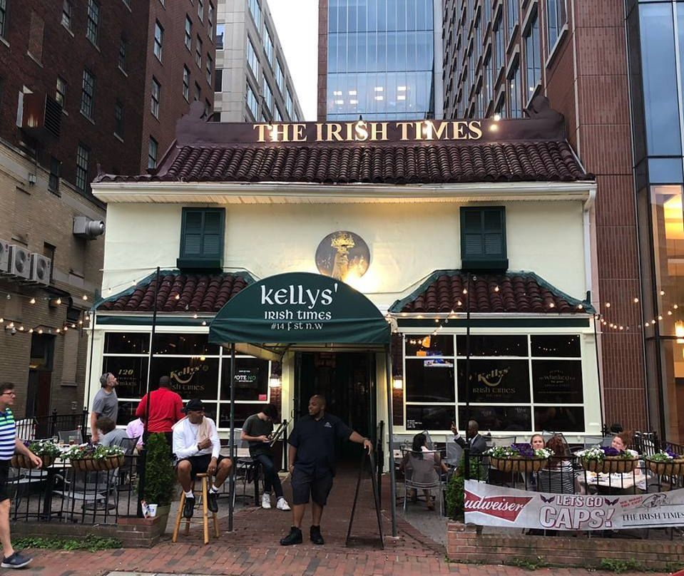 The front entrance of Kelly's Irish Times, complete with outdoor seating and a green awning.