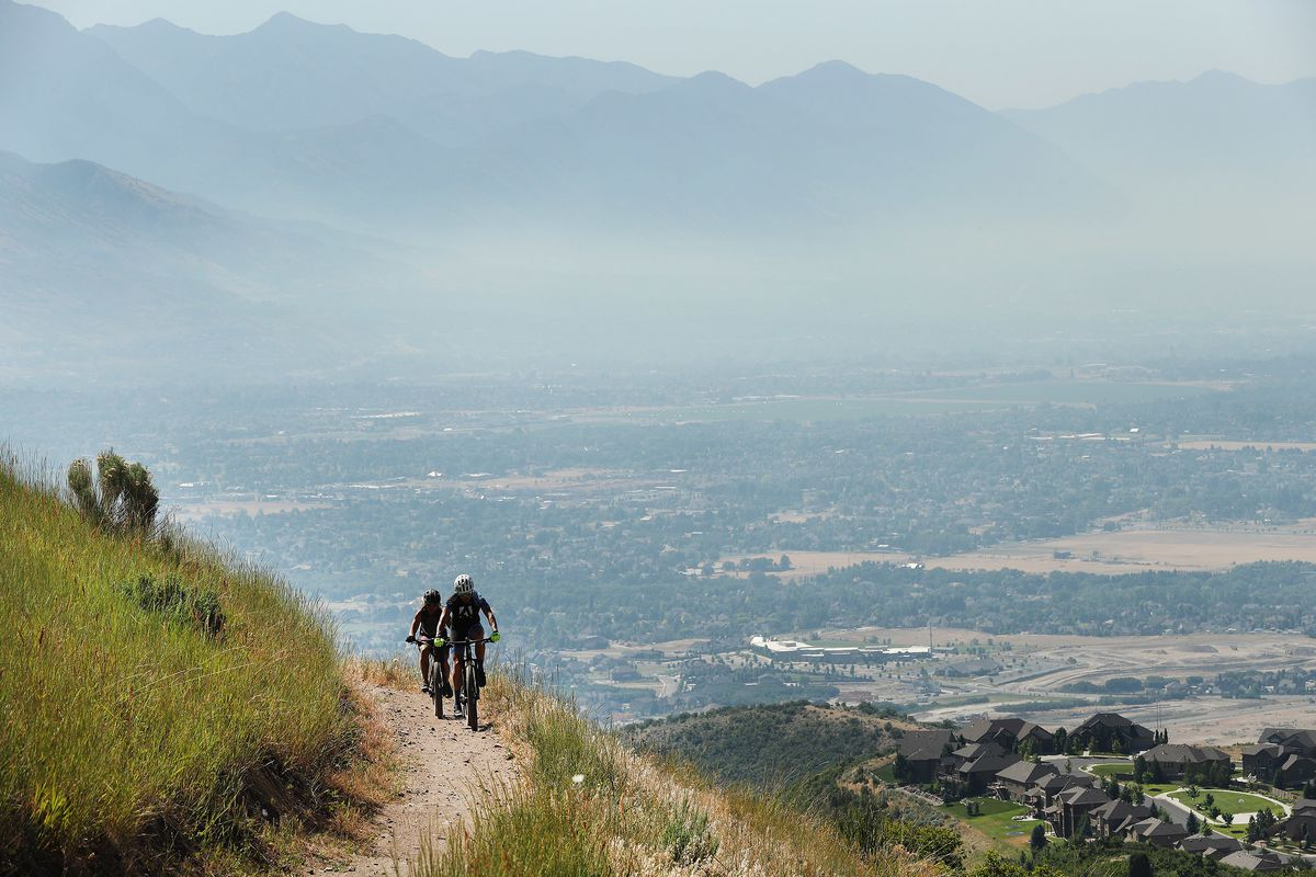 Cyclists ride the Eagle Crest Trail that offers a view of smoke-filled Utah County on Friday, July 6, 2018.