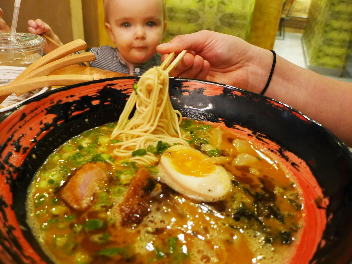 Chopsticks lift noodles out of a bowl of curried ramen as a baby looks on.