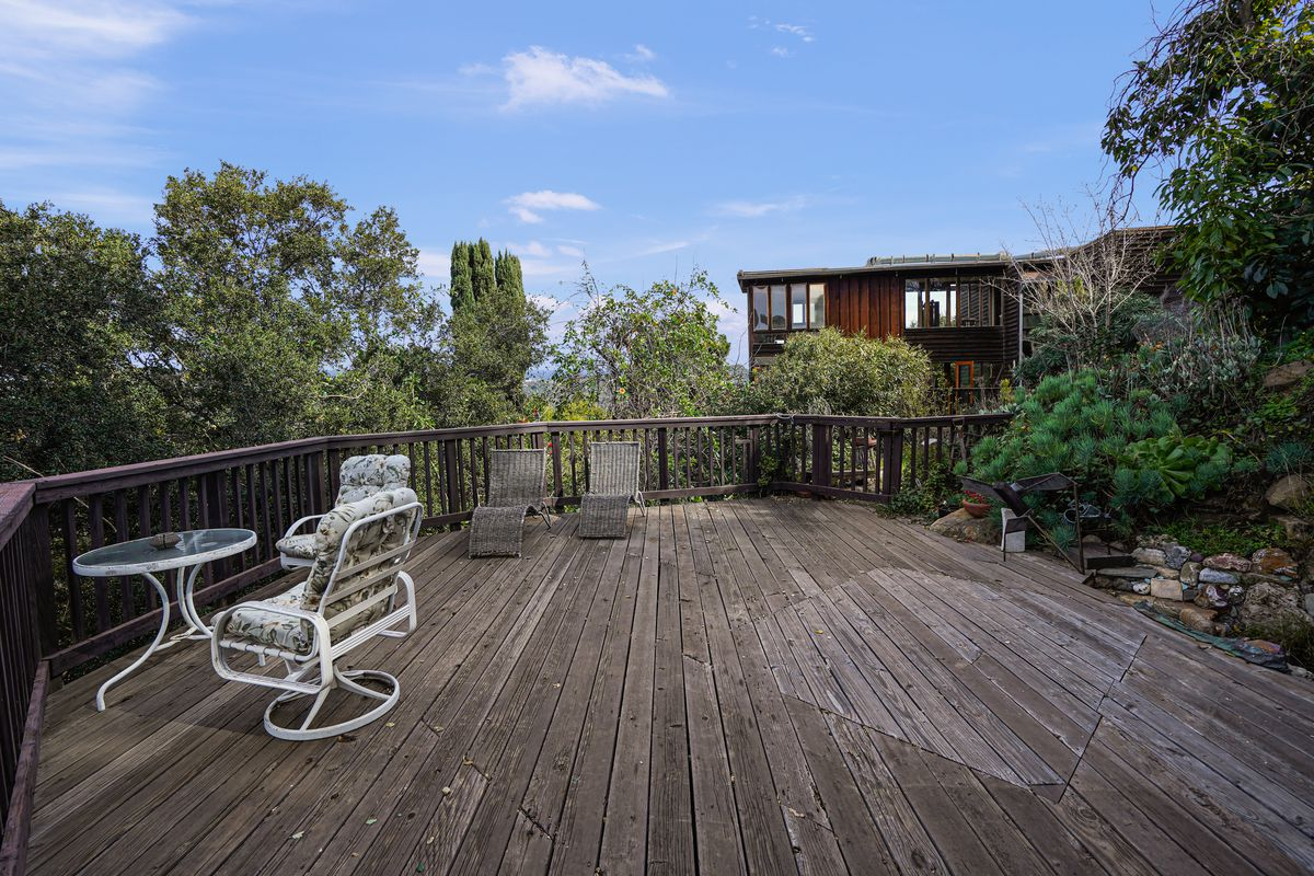 A wooden deck with a small table and chairs