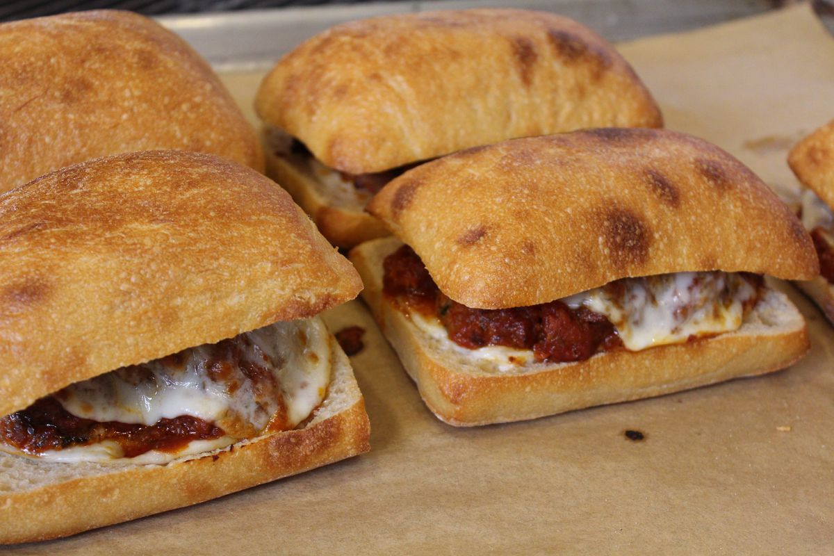Four meatball sandwiches, oozing with melted white cheese