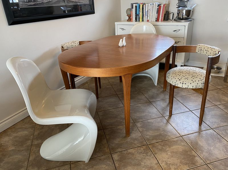 An oval wooden dining table is surrounded by wooden chairs with cream cushions and white curved plastic chairs.