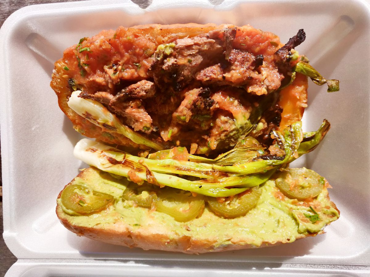 Overhead view of a Mexican sandwich, open to reveal guacamole, grilled whole scallions, and more.