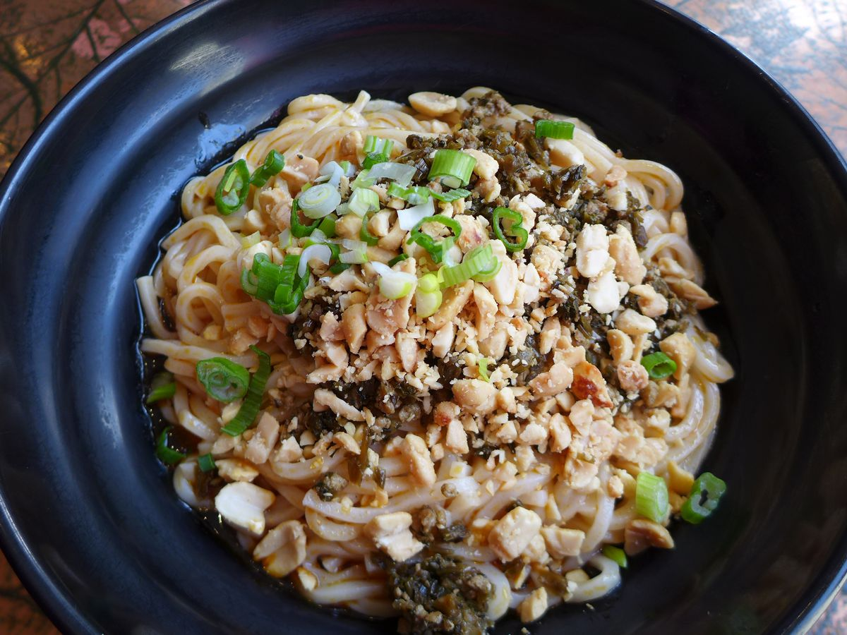 A bowl of noodles with crushed peanuts and scallions on top.