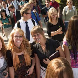 Three BYU-Idaho students pose for a picture after devotional as swarms of people walk past on Sept. 29, 2009.
